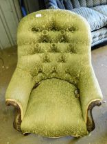 A Victorian button back armchair, the mahogany carved arms, with a gold ribbon border, on green dama