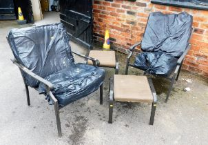 Two metal framed outdoor chairs with footstools and cushions.