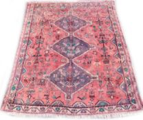 A Persian rug, with a central pole medallion, on a red ground with one wide and one narrow border,
