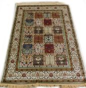 A machine woven mercerised cotton rug, in the Persian style, decorated with flowers, within