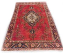 A Persian rug, with a central pole medallion in navy, on a red ground decorated with flowers,