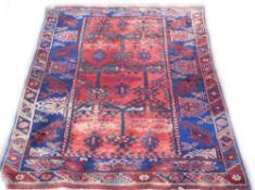 A Persian rug, with a central pole medallion in navy, on a red ground with one wide and one narrow