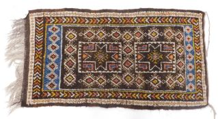 A Turkoman style small rug, with a design of medallions on a brown ground with one wide, one