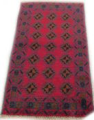 A Turkish style rug, with a design of three rows of medallions, on a red ground with multiple