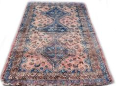 A Persian rug, with a central pole medallion in navy, on a red ground with multiple borders, 248cm x