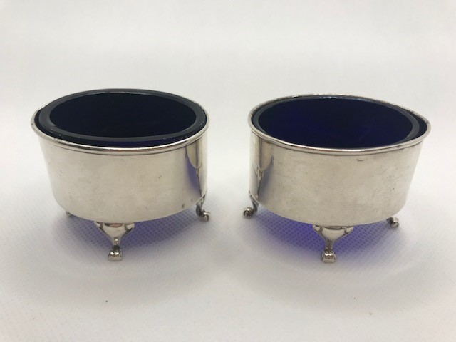 Pair of Oval Silver hallmarked salts each on three scroll feet with Blue glass liners