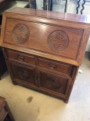 Imported Chinese rosewood bureau with carved detailing, two drawers and two cupboards under