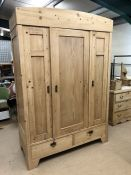 Large pine wardrobe with hanging and shelving space and two drawers to base, approx 140cm wide x