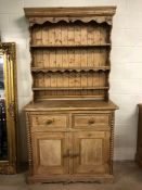 Antique pine dresser with three shelves over, two drawers and two cupboards below, with carved