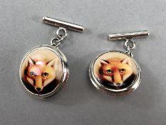 A pair of silver and enamel fox cufflinks