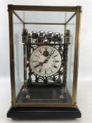 A skeleton movement rolling ball table clock with cloisonné posts and finials in glass case. Clock