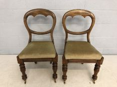 Pair of Victorian pine balloon backed chairs with turned front legs on original castors
