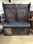 Carved oak settle with high back and padded seat, approx 133cm x 45cm x 150cm tall