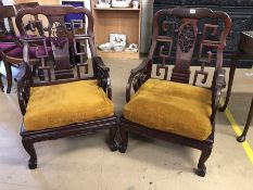 Pair of Chinese heavily carved low armchairs, each approx 63cm wide x 95cm tall x 57cm deep