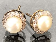 Pair of Pearl earrings surrounded by a ring of Diamonds