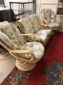 Cane conservatory suite comprising two seater sofa and a pair of swivel armchairs