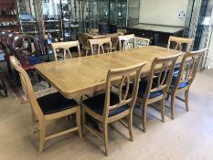 Large modern pine extending dining table on twin pedestal base with eight matching chairs with