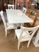 White Ikea folding table with internal drawer space and four white chairs