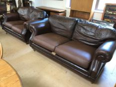 Three seater and two seater brown leather sofas on castors by Thomas Lloyd, the larger approx