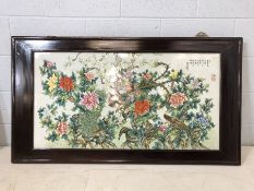 Large framed Chinese porcelain plaque depicting birds and blossom with Chinese script, approx