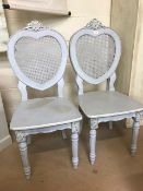 Two carved painted rattan backed heart shaped decorative chairs
