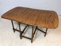 Drop leaf light oak table with turned detailing to legs