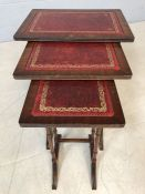 Nest of three red leather-topped side tables