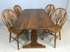 Refectory style dining table, possibly Ercol, with four wheel back dining chairs