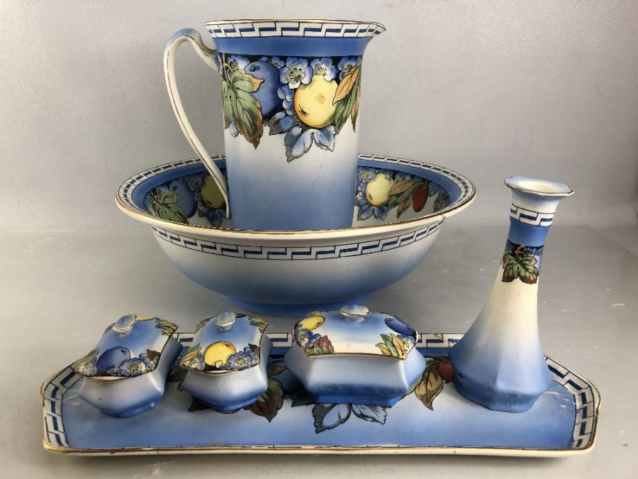 Dressing table set comprising jug, bowl, tray, pots, vase etc with colourful fruit design (A/F)