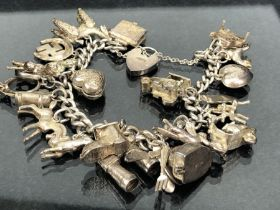"""Silver charm bracelet with approx 20 charms mostly marked """"silver"""" (approx 84g)"""