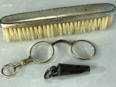 Gold metal vintage spectacles with a silver hallmarked brush and a silver whistle