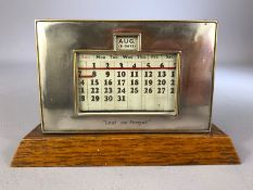 1930s perpetual calendar on wooden plinth with silver plate frame inscribed 'Lest we Forget', approx