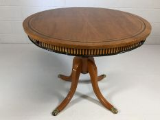 Modern circular table on four curved legs with lion paw detailing to feet and two slim drawers,