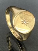 9ct Gold signet ring with starburst design and set with a single diamond to centre approx size 'R' &