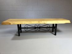 Rustic coffee table on wrought iron base with the top a section of a tree trunk