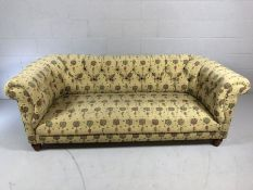 Chesterfield style three seater sofa with button back and plant design fabric upholstery, approx