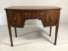 Small mahogany bow-fronted side board with two cupboards and single drawer on square tapering