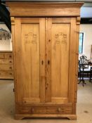 Pine wardrobe with two hanging rails and carved detail to doors, with key and drawer under, approx