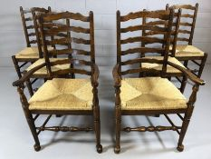 Set of six oak ladder back chairs with rush seats and turned stretchers, two carvers