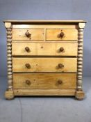 Pine chest of five drawers with turned columns to side on bun feet, approx 57cm x 115cm x 112cm