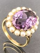 9ct Gold ring set with a large faceted Amethyst stone approx 16mm x 12mm and surrounded by seed