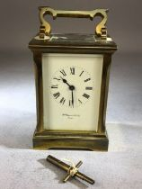 Carriage clock, with white enamel dial and Roman numerals, visible escapement and the rear plate