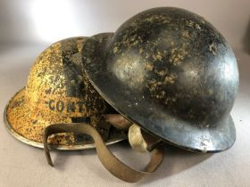 """Two Military WWII helmets one marked for Plasfort and bakelite the other metal reads the other """""""