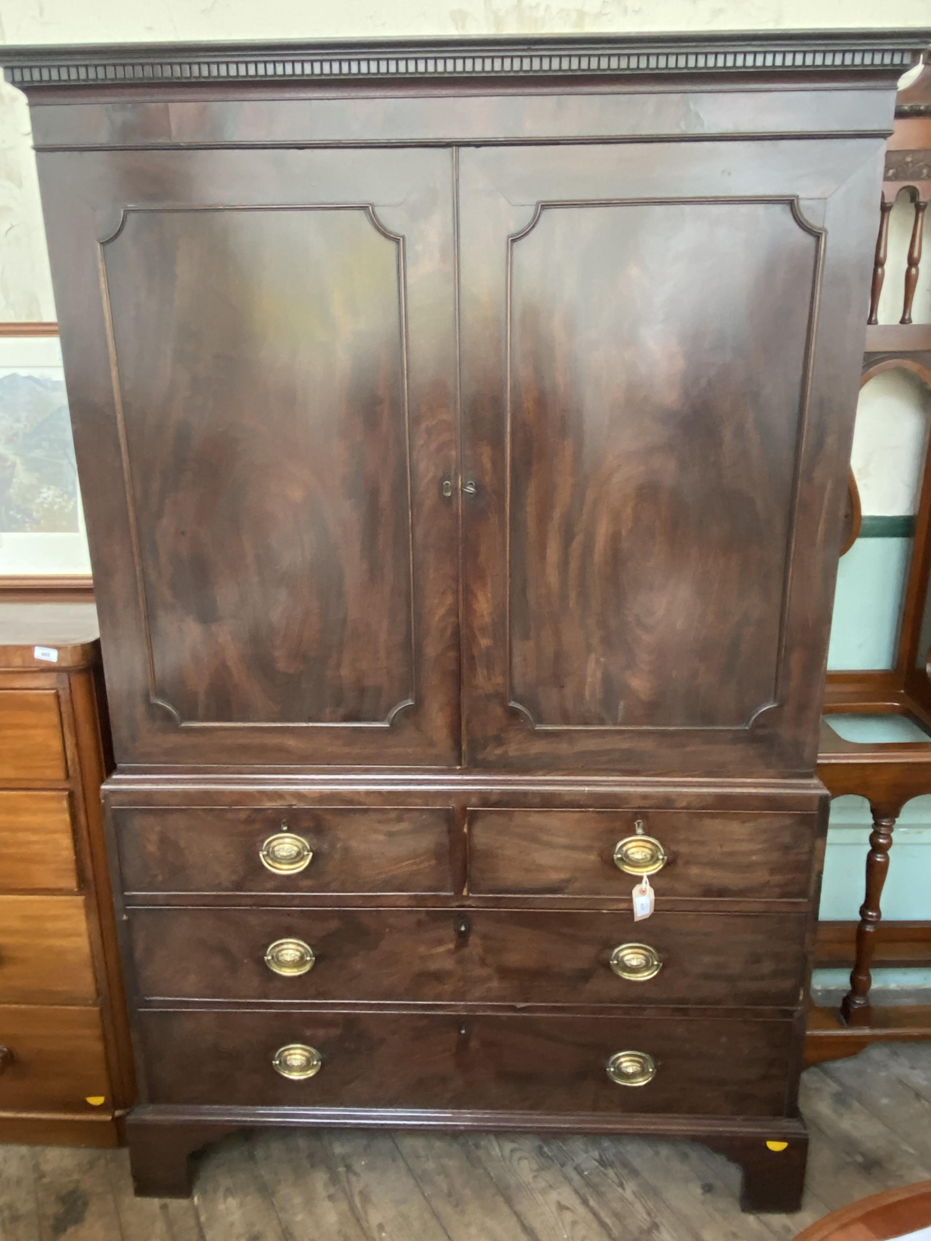 Figured mahogany linen press fitted 2 small and 2 long base drawers all with oval brass finger