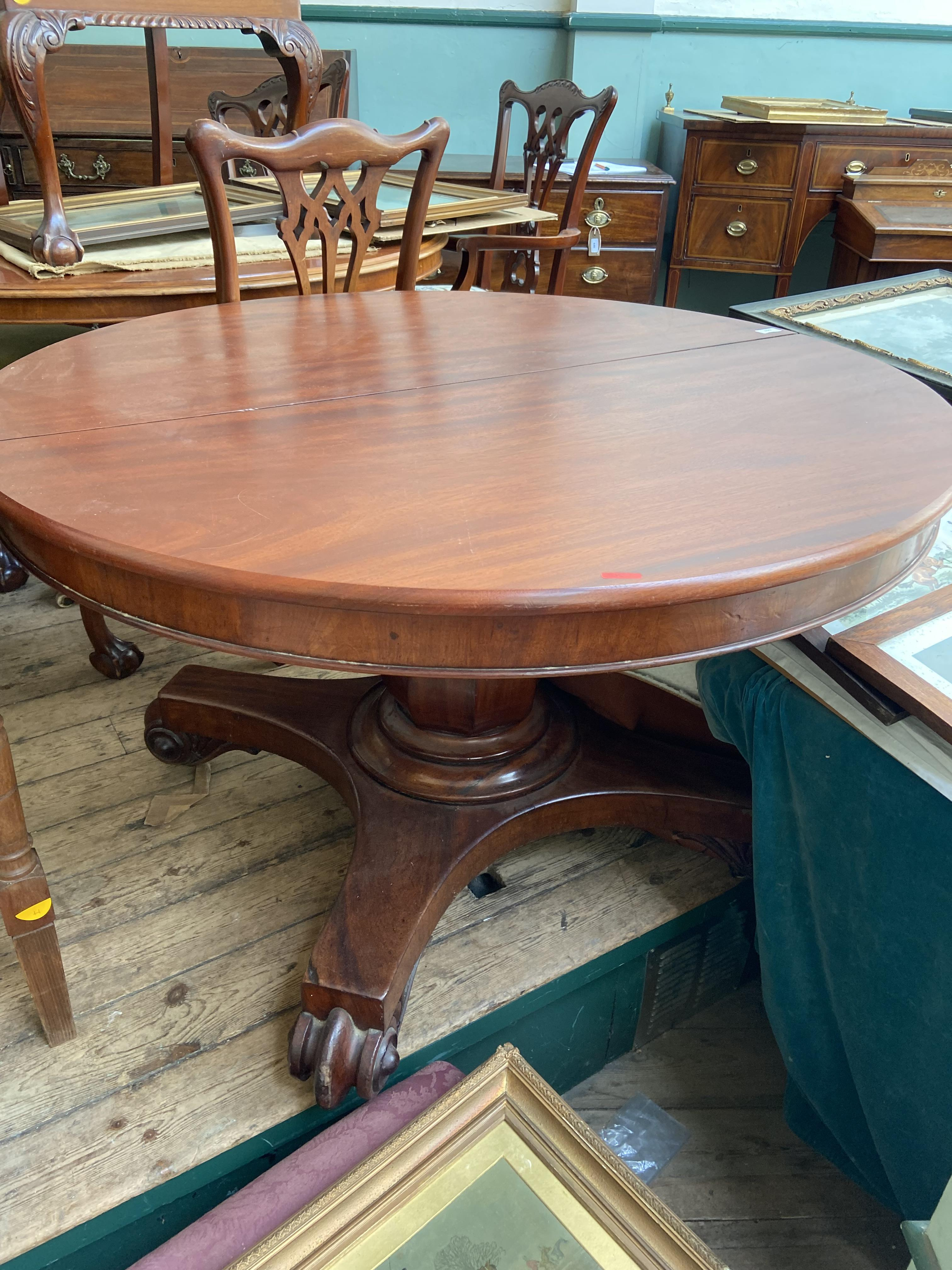 Circular topped dining table on 3 splayed claw feet offered with 3 spare leaves