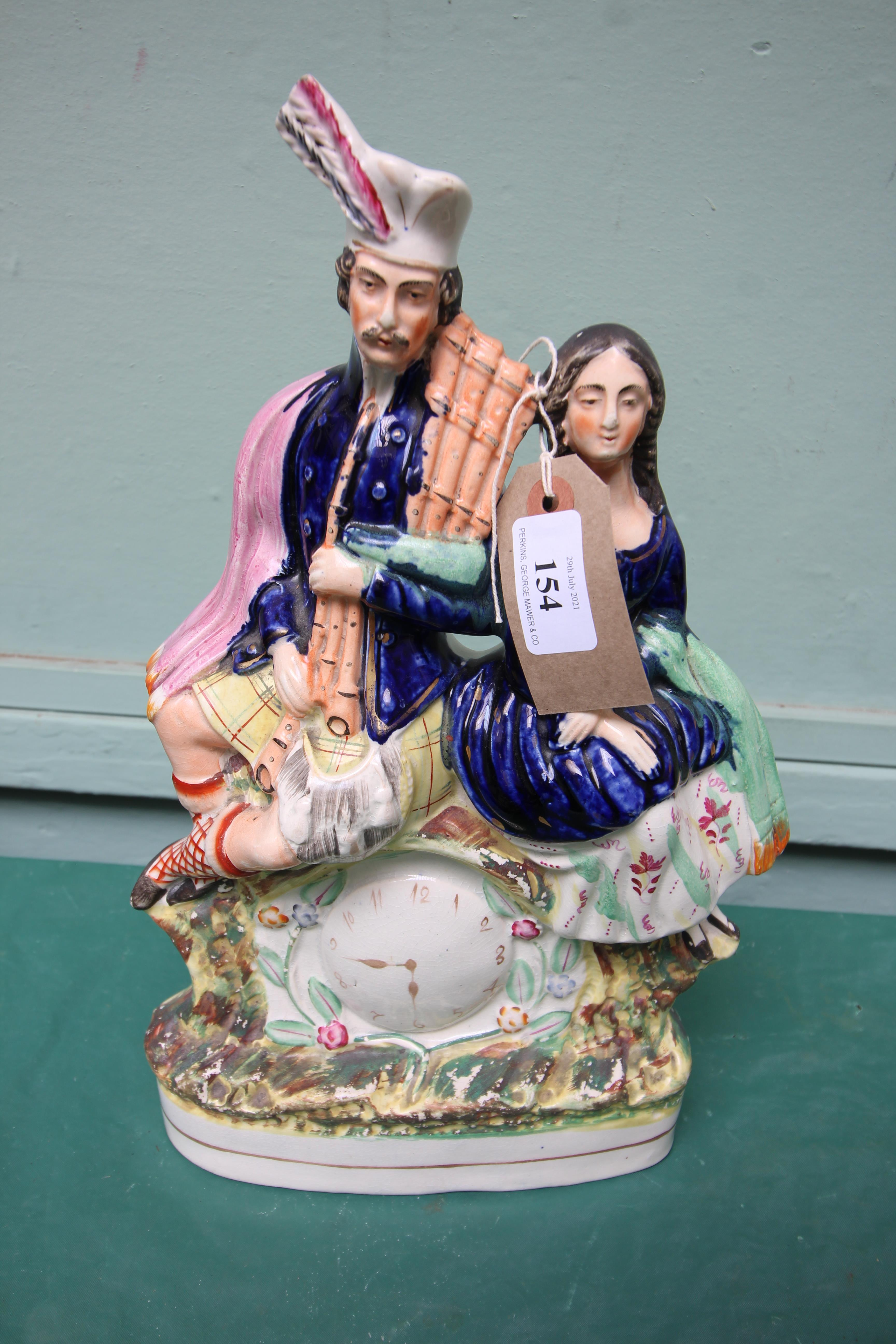 Large Staffordshire Victorian flatback 'clock' figure of a Scotsman and his lady companion