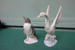 Lladro figure of a penguin and a Nao figure of an alighting swan