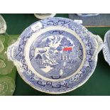 Circular blue and white willow patterned serving dish on circular raised plinth and plate