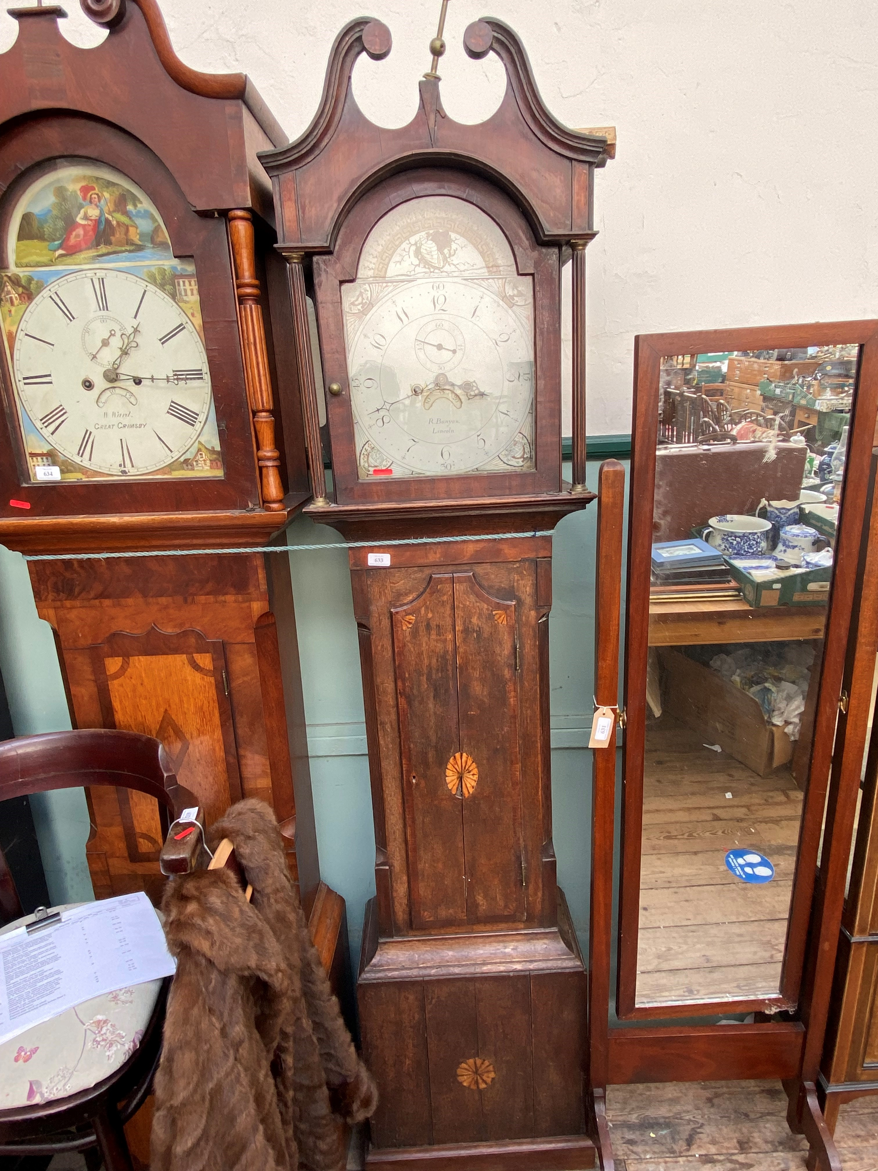 Long cased clock in mixed woods with swan neck pediment and brass finial,
