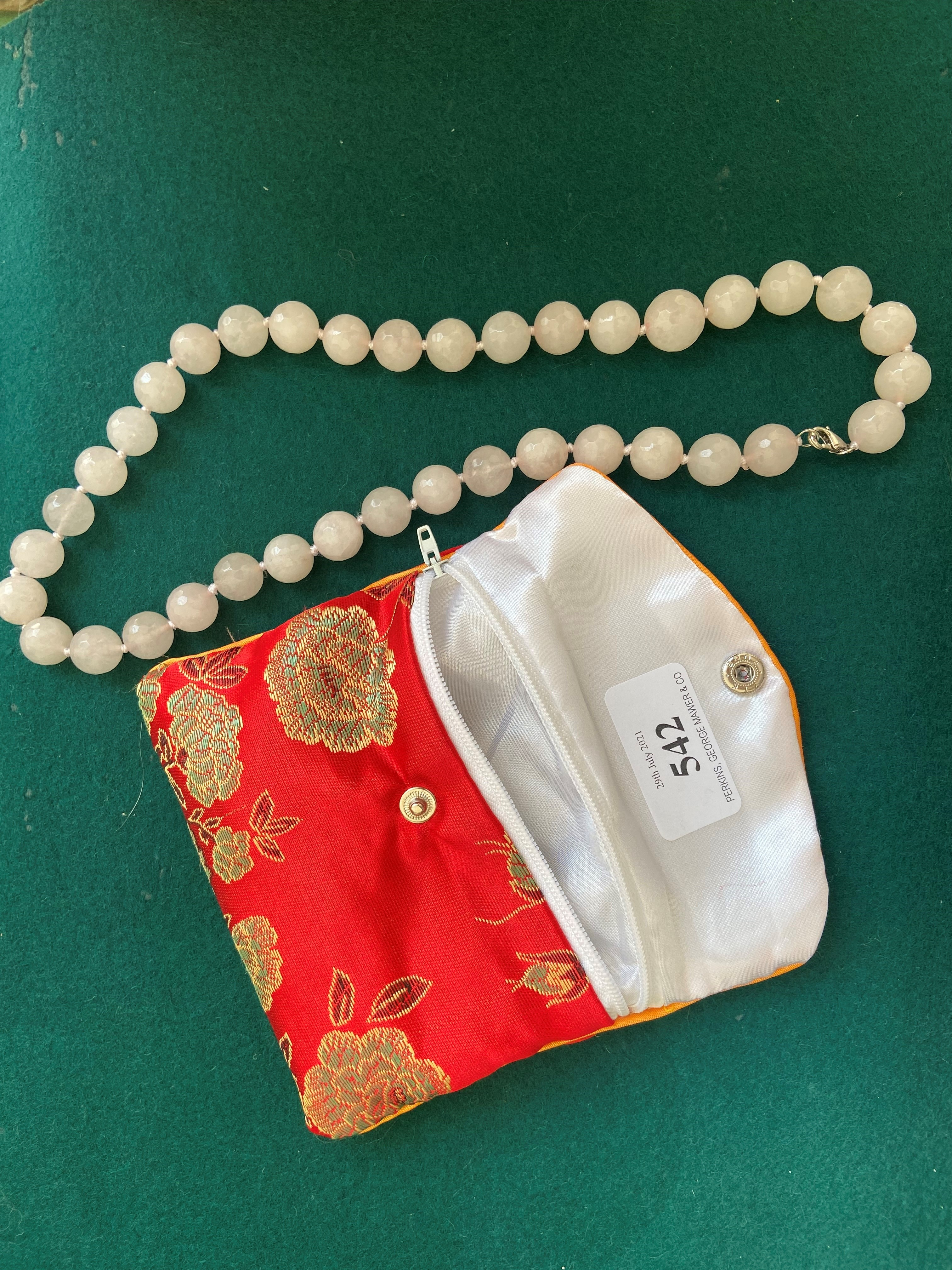 Silk purse containing single strand voilet bead necklace